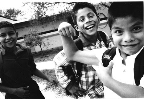 Sort-hvitt fotografi som viser små og lekne gutter viser frem små muskeler som blir store