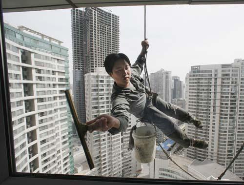 Foto av Reinhard Krause viser en mann som vasker vinduer i høyblokker.